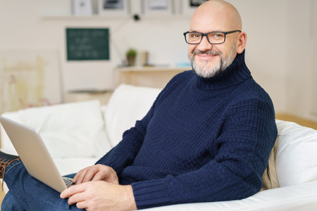 man with a goatee: Middle-aged balding man with a goatee relaxing at home on a sofa with his laptop computer smiling at the camera