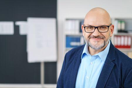 Vrolijke middelbare leeftijd knappe man met baard en kaal hoofd in business casual outfit in luchtige kantoorruimte Stockfoto