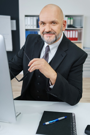 man working computer: Waist Up Portrait of Smiling Mature Businessman Wearing Suit and Holding Eyeglasses While Sitting at Computer Desk with Notebook and Pen in Modern Workplace Office