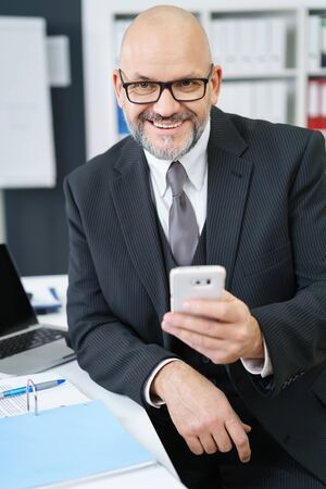 Waist Up Portrait of Smiling Mature Businessman with Facial Hair Wearing Suit and Eyeglasses and Holding Cell Phone While Sitting at Desk with Laptop and Notebook in Office Workplace