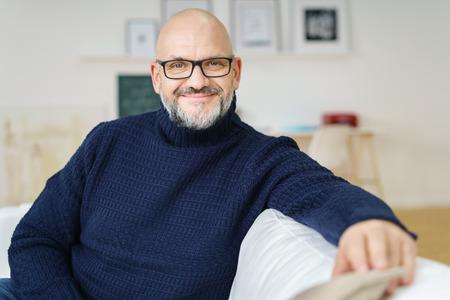 Relaxed aantrekkelijke kale man van middelbare leeftijd draagt een bril met een vriendelijke glimlach, zittend op een bank in zijn woonkamer lachend naar de camera