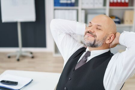 Contented businessman relaxing in the office reclining in his chair with his hands clasped behind his head and eyes closed smiling in pleasure Stock Photo