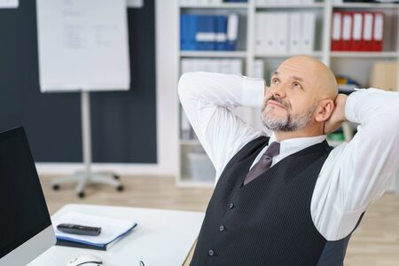 hands on head: Waist Up of Mature Businessman with Facial Hair Wearing Suit Sitting and Taking a Break with Hands Behind Head Looking Relaxed at Computer Desk in Modern Office Workplace