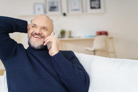 relajado: hombre de mediana edad guapo en el bigote y la barba con la mano detrás de la cabeza mientras mira hacia arriba en la conversación en el teléfono celular en el interior