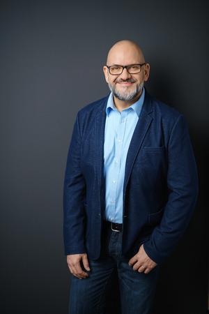 Dreiviertelansicht Porträt zuversichtlich Älterer Mann mit Bart und Brille Tragen Business Casual Kleidung und Stehen im Studio mit dunkelgrauem Hintergrund und Textfreiraum Standard-Bild