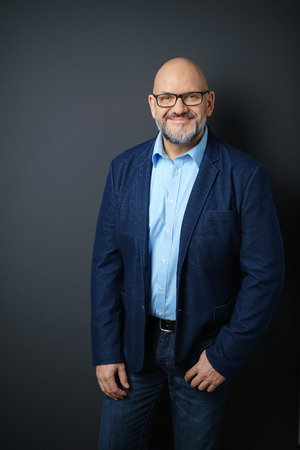 man 40 50: Three Quarter Length Portrait of Confident Mature Man with Facial Hair and Eyeglasses Wearing Business Casual Clothing and Standing in Studio with Dark Gray Background and Copy Space