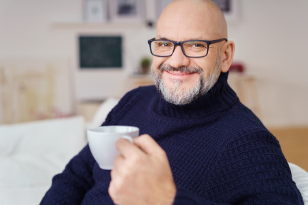 Happy attractive bald middle-aged man wearing glasses enjoying coffee looking at the camera with a beaming smile of pleasure