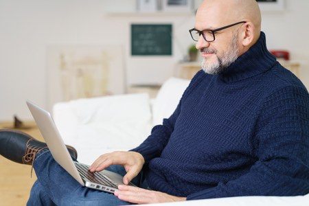 Grinning middle aged bald and bearded attractive man in blue sweater typing on metallic finish laptop while seated on sofa