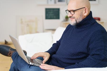 hombres maduros: Sonriendo atractivo hombre calvo y barbudo de mediana edad en azul escribiendo en la computadora portátil suéter acabado metálico mientras se está sentado en el sofá