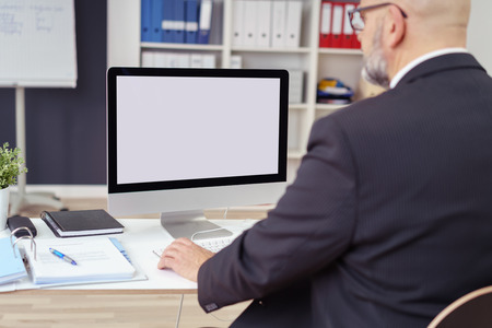 Сзади по мнению плеча бизнесмен, работающий на своем столе в офисе с акцентом на его рабочем столе пустой монитор компьютера