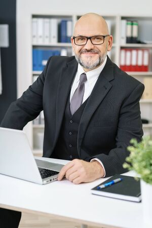 sitting at desk: Confident balding senior businessman with a beard seated at his desk in the office smiling at the camera