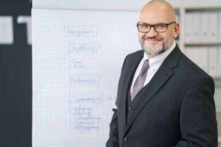Amigable de negocios mayor que da una presentación con un rotafolio en la oficina que se inclina hacia la cámara con una sonrisa Foto de archivo