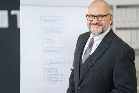 training business: Friendly senior businessman giving a presentation with a flip chart in the office leaning towards the camera with a smile Stock Photo