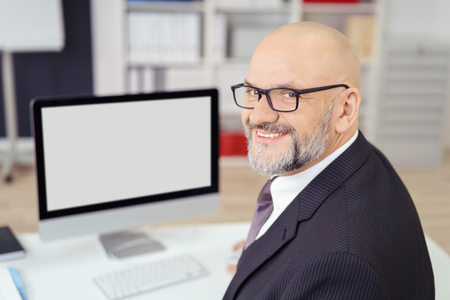 Successful businessman with a lovely friendly smile turning in his chair at the office to look at the camera, blank computer screen visible