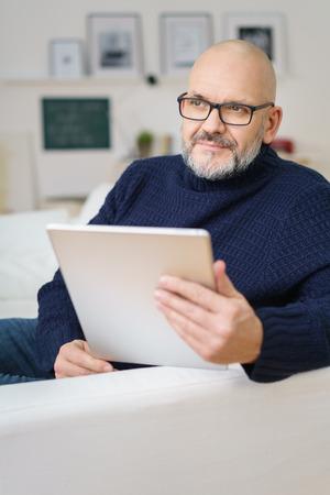 Doordachte man van middelbare leeftijd ontspannen thuis op een bank in de woonkamer met een tablet-pc en op zoek naar de kant met een contemplatieve uitdrukking