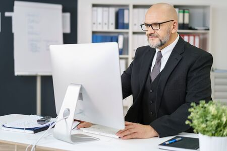 man 40 50: Diligent senior businessman working at his desk in the office on a desktop computer, reading information on the monitor