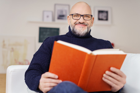 Handsome man wearing glasses relaxing at home reading a book on a sofa in the living room looking at the camera with a warm friendly smile Standard-Bild