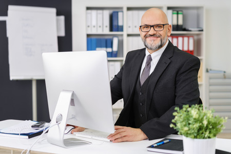 Attractive balding businessman working at his desk in the office on a desktop computer looking across at the camera with a friendly smile Foto de archivo