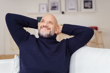 man with a goatee: Attractive middle-aged man with a goatee sitting daydreaming as he relaxes at home staring up into the air with a smile of pleasure