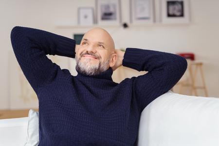 Attraktiver Mann mittleren Alters mit einem Ziegenbart, der träumend sitzt, während er sich zu Hause entspannt und mit einem Lächeln der Freude in die Luft starrt Standard-Bild