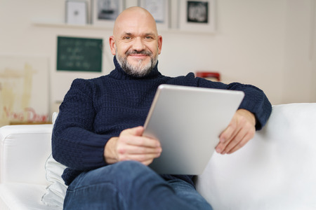 Middle-aged balding man with a goatee and glasses relaxing at home on a comfortable sofa with a tablet computer smiling at the camera Foto de archivo