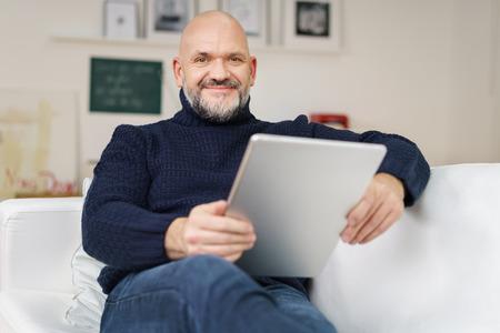 Middelbare leeftijd kalende man met een sikje en een bril ontspannen thuis op een comfortabele bank met een tablet-computer lachend naar de camera