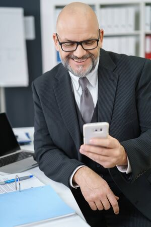 mobile business: Waist Up of Smiling Mature Businessman with Facial Hair Wearing Suit and Eyeglasses and Looking Down at Cell Phone While Sitting at Desk with Laptop and Notebook in Office Workplace