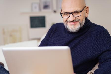 Primer plano de hombre maduro con pelo gris facial llevaba anteojos y Azul marino cuello alto suéter sonriendo a la pantalla del ordenador portátil de la comodidad del hogar Foto de archivo
