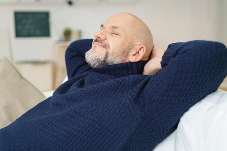 hombre feliz disfrutando de un feliz descanso sentado en un cómodo sofá juntando las manos detrás de su cuello con los ojos cerrados y una sonrisa de satisfacción, vista lateral