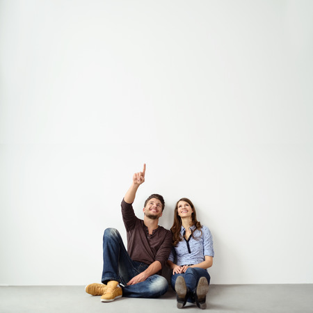 home purchase: Young couple sitting on the ground leaning against an exterior white all with copy space pointing up into the air and smiling