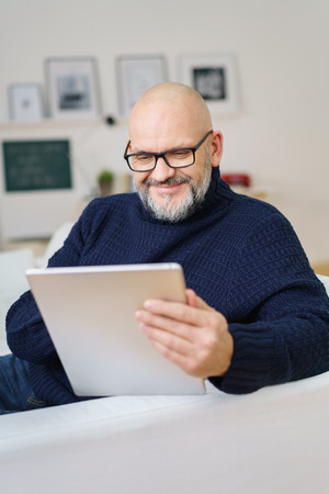 goatee: Attractive bald middle-aged man with a goatee beard and glasses relaxing with a tablet computer on his sofa at home reading the data with a smile