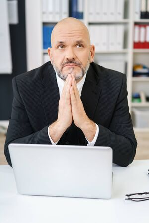 deep thought: Single pensive middle aged businessman in front of open laptop with palms together under chin while looking up in deep thought