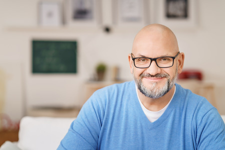 Head and Shoulders Portrait of Mature Man with Gray Facial Hair Wearing Eyeglasses and Casual Blue Shirt Smiling at Camera in Living Room on Relaxing Day at Home, Copy Space to Left of Image