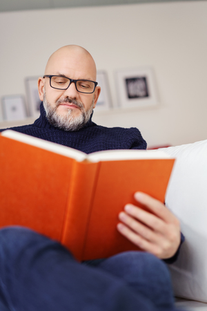 goatee: Middle-aged man with a goatee beard wearing glasses relaxing at home on the sofa with a good book, focus to his face