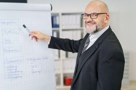 business training: Single mature businessman with beard, eyeglasses and bald head looking at camera while pointing at large chart with marker