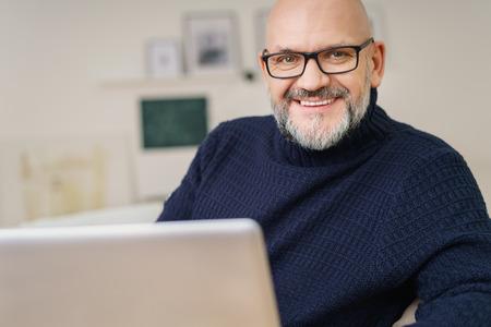 calvo: Atractivo hombre de mediana edad con una perilla y gafas descansando en su casa con su ordenador portátil mirando a la cámara con una cálida sonrisa radiante