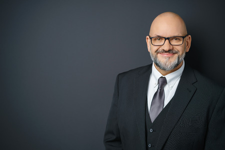 Waist Up Portrait of Mature Businessman with Facial Hair Wearing Suit and Eyeglasses Smiling Confidently at Camera and Standing in Studio with Dark Gray Background with Copy Space Stock Photo