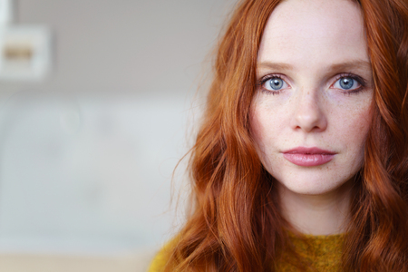 Gorgeous young redhead woman with long coppery hair and blue eyes looking at the camera, close up head shot with copy space