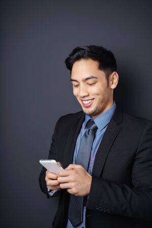 handphone: Smiling Asian businessman reading his text messages on his mobile phone as he stands relaxing against a dark studio background with copy space Stock Photo