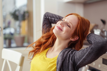 grins: Beautiful young female in gray sweater and long red hair closes her eyes and grins while stretching with hands behind her head in kitchen