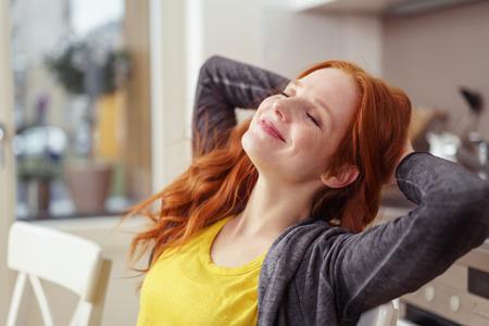 Krásná mladá žena v šedém svetru a dlouhé rezavé vlasy, zavře oči a úsměvy, zatímco protahování s rukama za hlavou v kuchyni