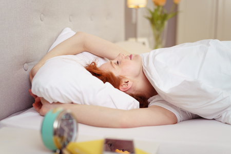 view of a comfortable bedroom: Side Profile View of Young Woman with Red Hair Sleeping in Comfortable Bed with Plush Duvet in Luxury Hotel Bedroom with Alarm Clock in Foreground - Woman Enjoying Sleeping In on Weekend
