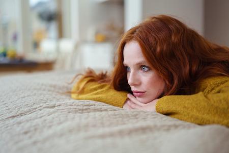 Atractiva mujer joven pelirroja acostado en su cama en su estómago pensando apoyando la barbilla en las manos y mirando a lo lejos