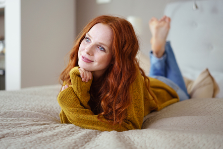 faraway: Pretty young woman lying on her stomach on her bed daydreaming with a happy smile and faraway look Stock Photo