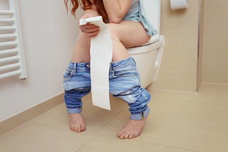 pied jeune fille: Close Up de Unrecognizable jeune femme avec Long Red Hair Serrant Tissue de papier hygiénique dans la main, assis sur Toilette avec Jeans Autour Chevilles Salle de bains Banque d'images