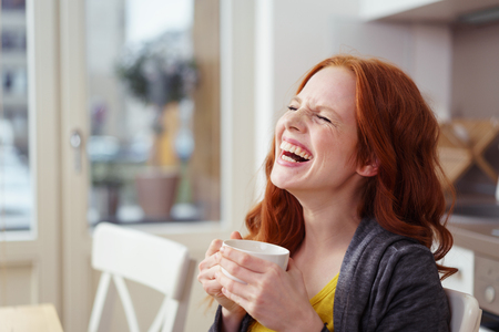 people laughing: Spontaneous attractive young redhead woman enjoying a good laugh over a morning cup of coffee at home in the apartment