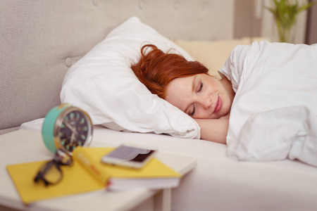 girl bed: Attractive redhead woman sleeping in bed with a serene smile on her face and an alarm clock on the table alongside