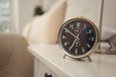 Alarm clock set for an early morning wake up call at seven standing on a bedside table Stock Photo