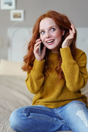 red haired: Happy pretty vivacious young woman chatting to a friend on her mobile phone as she relaxes on her bed at home