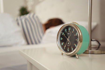 Alarm clock about to ring alongside a sleeping person in bed with focus to the bedside table ad clock
